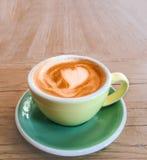 Φλιτζάνι του καφέ με τον αφρό σχεδίων καρδιών σε ένα κίτρινο φλυτζάνι σε αγροτικό Στοκ φωτογραφία με δικαίωμα ελεύθερης χρήσης