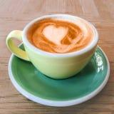 Φλιτζάνι του καφέ με τον αφρό σχεδίων καρδιών σε ένα κίτρινο φλυτζάνι σε αγροτικό Στοκ Εικόνα