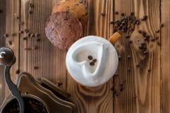 Φλιτζάνι του καφέ με τον αφρό υπό μορφή καρδιάς με τα μπισκότα και φασόλια καφέ με το μύλο καφέ σε έναν ξύλινο πίνακα Στοκ φωτογραφία με δικαίωμα ελεύθερης χρήσης