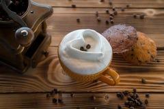 Φλιτζάνι του καφέ με τον αφρό υπό μορφή καρδιάς με τα μπισκότα και φασόλια καφέ με το μύλο καφέ σε έναν ξύλινο πίνακα Στοκ Φωτογραφίες