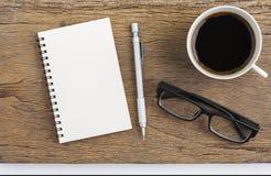 Φλιτζάνι του καφέ με το μολύβι σημειωματάριων και γυαλιά στον πίνακα ξύλινο Στοκ Φωτογραφίες