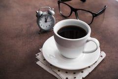 Φλιτζάνι του καφέ με το ξυπνητήρι στον πίνακα και τα μαύρα γυαλιά Στοκ φωτογραφία με δικαίωμα ελεύθερης χρήσης