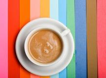 Φλιτζάνι του καφέ με το ποτό γάλακτος ή cappuccino σε ζωηρόχρωμο ως υπόβαθρο ουράνιων τόξων Δόση της ενεργειακής έννοιας Ποτό με Στοκ φωτογραφία με δικαίωμα ελεύθερης χρήσης