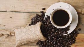 Φλιτζάνι του καφέ με το σωρό των φασολιών καφέ στον ξύλινο πίνακα απόθεμα βίντεο