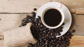 Φλιτζάνι του καφέ με το σωρό των φασολιών καφέ φιλμ μικρού μήκους