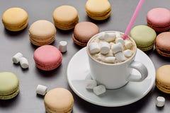 Φλιτζάνι του καφέ με το marshmelow, το άχυρο και ζωηρόχρωμα γαλλικά macaroons, στο γκρίζο υπόβαθρο Στοκ Εικόνες