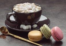Φλιτζάνι του καφέ με marshmallows, κουτάλι και χρωματισμένα γαλλικά macaroons, στο γκρίζο υπόβαθρο Στοκ φωτογραφία με δικαίωμα ελεύθερης χρήσης