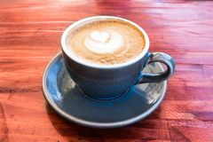 Φλιτζάνι του καφέ που εξυπηρετείται στο μπλε κεραμικό φλυτζάνι στον ξύλινο πίνακα Στοκ φωτογραφία με δικαίωμα ελεύθερης χρήσης