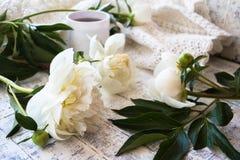 Φλιτζάνι του καφέ πρωινού και όμορφα άσπρα peonies σε έναν άσπρο ξύλινο πίνακα στοκ εικόνα