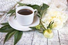 Φλιτζάνι του καφέ πρωινού και όμορφα άσπρα peonies σε έναν άσπρο ξύλινο πίνακα στοκ φωτογραφία με δικαίωμα ελεύθερης χρήσης