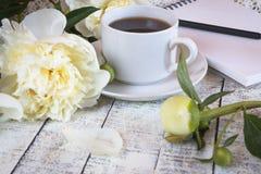 Φλιτζάνι του καφέ πρωινού και όμορφα άσπρα peonies σε έναν άσπρο ξύλινο πίνακα στοκ φωτογραφίες