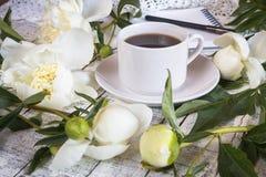 Φλιτζάνι του καφέ πρωινού και όμορφα άσπρα peonies σε έναν άσπρο ξύλινο πίνακα στοκ φωτογραφίες με δικαίωμα ελεύθερης χρήσης