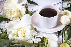 Φλιτζάνι του καφέ πρωινού και όμορφα άσπρα peonies σε έναν άσπρο ξύλινο πίνακα στοκ εικόνες