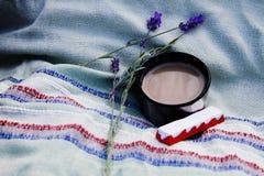 Φλιτζάνι του καφέ, σοκολάτα και ένας κλάδος lavender στη φύση στοκ εικόνα