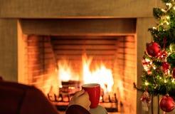 Φλιτζάνι του καφέ στο χριστουγεννιάτικο δέντρο και το καίγοντας υπόβαθρο εστιών Στοκ Εικόνες