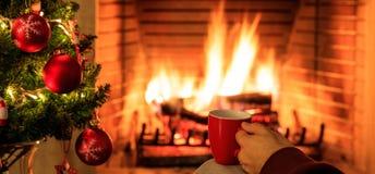 Φλιτζάνι του καφέ στο χριστουγεννιάτικο δέντρο και το καίγοντας υπόβαθρο εστιών Στοκ Φωτογραφίες