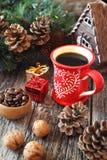 Φλιτζάνι του καφέ, φασόλια καφέ, κώνοι πεύκων και νέα διακόσμηση δέντρων έτους Στοκ Εικόνες