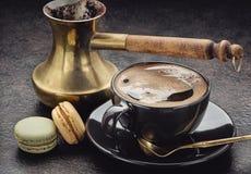 Φλιτζάνι του καφέ, turka κατασκευαστών καφέ με την ξύλινη λαβή, macaroons στη σκοτεινή επιφάνεια Στοκ Φωτογραφίες