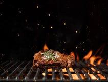 Φλογερό πλέγμα σχαρών με το κομμάτι της μπριζόλας βόειου κρέατος Στοκ φωτογραφία με δικαίωμα ελεύθερης χρήσης