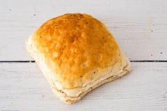 Φλοιώδης ρόλος ψωμιού σε έναν λευκό ξύλινο πίνακα στοκ φωτογραφία με δικαίωμα ελεύθερης χρήσης
