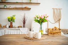 Φλυτζάνια και φρούτα προγευμάτων Τουλίπες άνοιξη στον πίνακα Ξύλινος πίνακας σε μια φωτεινή κουζίνα αγροτικός-ύφους Σκανδιναβικό  στοκ φωτογραφία με δικαίωμα ελεύθερης χρήσης