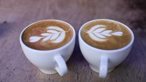 Φλυτζάνια καφέ με την τέχνη Latte στον πίνακα στην κινηματογράφηση σε πρώτο πλάνο καφέδων απόθεμα βίντεο