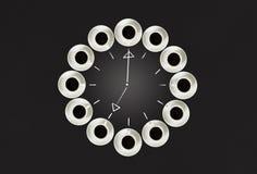 Φλυτζάνια με τον καφέ, που συσσωρεύεται σε έναν κύκλο Το ρολόι αποτελείται από είκοσι φλυτζάνια Μαύρη ανασκόπηση Χρόνος έννοιας σ Στοκ φωτογραφίες με δικαίωμα ελεύθερης χρήσης