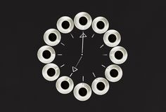 Φλυτζάνια με τον καφέ, που συσσωρεύεται σε έναν κύκλο Το ρολόι αποτελείται από είκοσι φλυτζάνια Μαύρη ανασκόπηση Χρόνος έννοιας σ Στοκ εικόνες με δικαίωμα ελεύθερης χρήσης