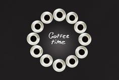 Φλυτζάνια με τον καφέ, που συσσωρεύεται σε έναν κύκλο Το ρολόι αποτελείται από είκοσι φλυτζάνια Μαύρη ανασκόπηση Χρόνος έννοιας σ Στοκ φωτογραφία με δικαίωμα ελεύθερης χρήσης