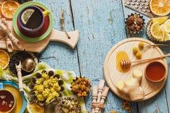 Φλυτζάνια με το βοτανικό τσάι και τα κομμάτια του λεμονιού, των ξηρών χορταριών και των διαφορετικών διακοσμήσεων Στοκ εικόνες με δικαίωμα ελεύθερης χρήσης