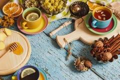 Φλυτζάνια με το βοτανικό τσάι και τα κομμάτια του λεμονιού, των ξηρών χορταριών και των διαφορετικών διακοσμήσεων Στοκ Φωτογραφίες