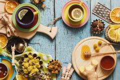 Φλυτζάνια με το βοτανικό τσάι και τα κομμάτια του λεμονιού, των ξηρών χορταριών και των διαφορετικών διακοσμήσεων Στοκ εικόνα με δικαίωμα ελεύθερης χρήσης
