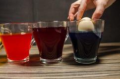 Φλυτζάνια με το χρωματισμένο νερό για Πάσχα στοκ εικόνες