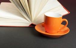 Φλυτζάνι για το τσάι ή τον καφέ και ανοικτό βιβλίο στο μαύρο υπόβαθρο η εκπαίδευση έννοιας βιβλίων απομόνωσε παλαιό Στοκ Εικόνες