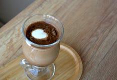 Φλυτζάνι γυαλιού ενός μαύρου καφέ με το γάλα σε έναν ξύλινο πίνακα Στοκ εικόνα με δικαίωμα ελεύθερης χρήσης