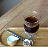 Φλυτζάνι γυαλιού ενός μαύρου καφέ με το γάλα σε έναν ξύλινο πίνακα Στοκ Εικόνα