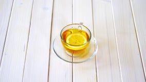 Φλυτζάνι γυαλιού με το τσάι παραδοσιακού κινέζικου και τη φέτα του λεμονιού στον άσπρο πίνακα απόθεμα βίντεο