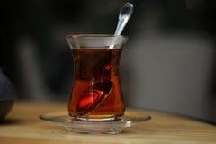 Φλυτζάνι γυαλιού του μαύρου τσαγιού, κουταλάκι του γλυκού στον ξύλινο πίνακα στοκ εικόνα