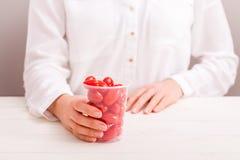 Φλυτζάνι εκμετάλλευσης επιχειρηματιών με τις φρέσκες μικρές ντομάτες στοκ φωτογραφία