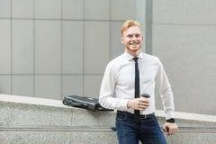 Φλυτζάνι εκμετάλλευσης επιχειρησιακών ατόμων ευτυχίας, εξετάζοντας τη κάμερα και το οδοντωτό χαμόγελο στοκ εικόνες με δικαίωμα ελεύθερης χρήσης
