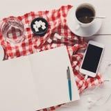Φλυτζάνι και smartphone καφέ στο ελεγμένο ύφασμα στο άσπρο ξύλο Στοκ Εικόνες