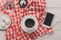 Φλυτζάνι και smartphone καφέ στο ελεγμένο ύφασμα στο άσπρο ξύλο Στοκ εικόνα με δικαίωμα ελεύθερης χρήσης