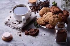 Φλυτζάνι καφέ, βάζο με τα φασόλια καφέ, μπισκότα πέρα από το άσπρο υπόβαθρο, εκλεκτική εστίαση, κινηματογράφηση σε πρώτο πλάνο, τ Στοκ Φωτογραφία
