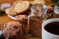 Φλυτζάνι καφέ, βάζο με τα φασόλια καφέ, μπισκότα πέρα από το αγροτικό υπόβαθρο, εκλεκτική εστίαση, κινηματογράφηση σε πρώτο πλάνο Στοκ Φωτογραφία