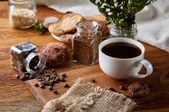 Φλυτζάνι καφέ, βάζο με τα φασόλια καφέ, μπισκότα πέρα από το αγροτικό υπόβαθρο, εκλεκτική εστίαση, κινηματογράφηση σε πρώτο πλάνο Στοκ Εικόνα