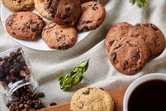 Φλυτζάνι καφέ, βάζο με τα φασόλια καφέ, μπισκότα πέρα από το αγροτικό υπόβαθρο, εκλεκτική εστίαση, κινηματογράφηση σε πρώτο πλάνο Στοκ φωτογραφίες με δικαίωμα ελεύθερης χρήσης
