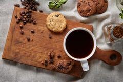 Φλυτζάνι καφέ, βάζο με τα φασόλια καφέ, μπισκότα πέρα από το αγροτικό υπόβαθρο, εκλεκτική εστίαση, κινηματογράφηση σε πρώτο πλάνο Στοκ εικόνα με δικαίωμα ελεύθερης χρήσης