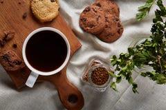 Φλυτζάνι καφέ, βάζο με τα φασόλια καφέ, μπισκότα πέρα από το αγροτικό υπόβαθρο, εκλεκτική εστίαση, κινηματογράφηση σε πρώτο πλάνο Στοκ Εικόνες