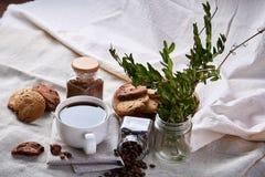 Φλυτζάνι καφέ, βάζο με τα φασόλια καφέ, μπισκότα στην άσπρη επιτραπέζια εκλεκτική εστίαση, κινηματογράφηση σε πρώτο πλάνο, τοπ άπ Στοκ φωτογραφία με δικαίωμα ελεύθερης χρήσης