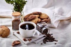 Φλυτζάνι καφέ, βάζο με τα φασόλια καφέ, μπισκότα στην άσπρη επιτραπέζια εκλεκτική εστίαση, κινηματογράφηση σε πρώτο πλάνο, τοπ άπ Στοκ φωτογραφίες με δικαίωμα ελεύθερης χρήσης